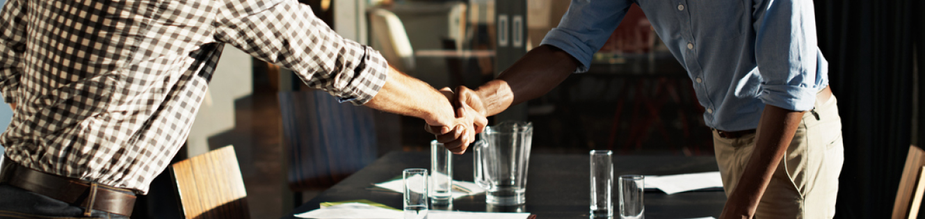 Two men shaking hands in a conference room header image