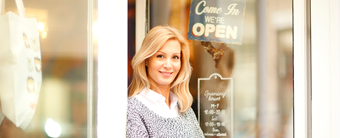 woman standing in front of storefront we're open sign header image