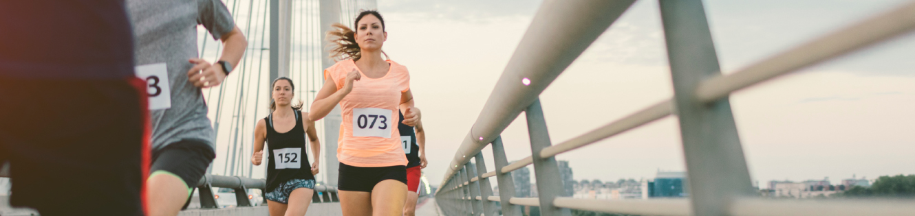 A woman running a marathon on a cloudy day header image