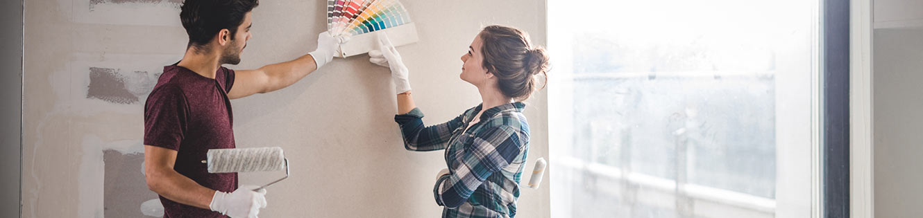 Couple looking at paint samples on wall header image